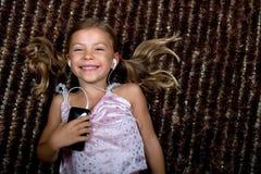 Kleines Mädchen, das Musik auf einem MP3-Player hört Lizenzfreies Stockbild