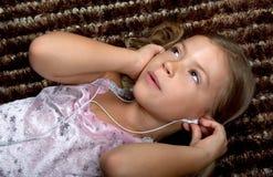 Kleines Mädchen, das Musik auf Kopfhörern hört Stockfoto