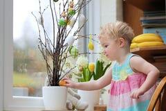 Kleines Mädchen, das nach Hause für Ostern verziert Stockbilder