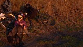 Kleines Mädchen, das nahe bei Fahrrad am Abend bei Sonnenuntergang sitzt stock video footage