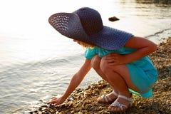 Kleines Mädchen, das nahe dem Wasser sitzt Stockbild