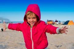 Kleines Mädchen, das nahe den Campingzelten auf dem Se läuft und lächelt Lizenzfreie Stockfotografie