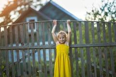 Kleines Mädchen, das nahe Dorfhäusern spielt lizenzfreie stockfotos