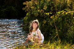 Kleines Mädchen, das nahe einem Strom spielt Stockfotografie