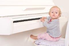 Kleines Mädchen, das nahe einem weißen Klavier sitzt Lizenzfreie Stockfotos
