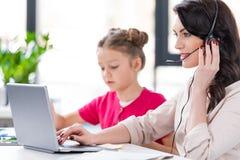 Kleines Mädchen, das nahe lächelnder Mutter im Kopfhörer arbeitet mit Laptop sitzt Lizenzfreie Stockfotografie