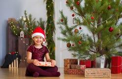 Kleines Mädchen, das nahe Weihnachtsbaum mit Geschenk in ihren Händen sitzt stockbild