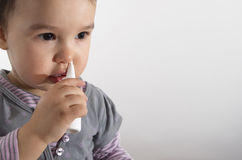 Kleines Mädchen, das nasalen Spray verwendet Lizenzfreies Stockbild