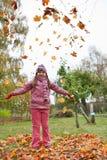 Kleines Mädchen, das oben Herbstblätter in einem Garten wirft Lizenzfreies Stockfoto