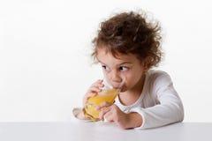 Kleines Mädchen, das Orangensaft trinkt Lizenzfreie Stockfotografie