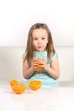 Kleines Mädchen, das Orangensaft trinkt Lizenzfreies Stockbild