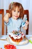 Kleines Mädchen, das Ostern-Kuchen verziert Stockbild