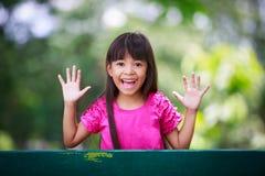 Kleines Mädchen, das Peekaboo spielt Stockbild