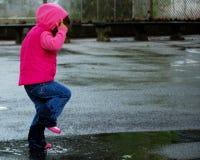 Kleines Mädchen, das in Pfütze 3 springt Stockfoto