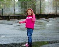 Kleines Mädchen, das in Pfütze springt Stockfotografie