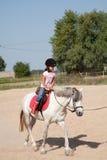 Kleines Mädchen, das Pferderuecken-Reitlektionen nimmt Lizenzfreies Stockfoto