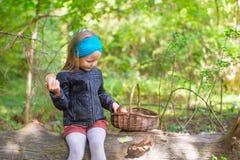 Kleines Mädchen, das Pilze in einem Herbst erfasst Stockfotografie