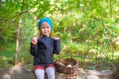Kleines Mädchen, das Pilze in einem Herbst erfasst Lizenzfreies Stockfoto