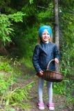 Kleines Mädchen, das Pilze im Herbstwald erfasst Stockfotografie