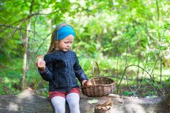 Kleines Mädchen, das Pilze im Herbstwald erfasst Stockbild