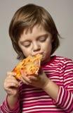 kleines Mädchen, das Pizza isst Stockbilder