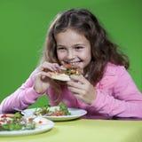Kleines Mädchen, das Pizza isst stockfotos