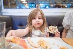 Kleines Mädchen, das Pizzastück mit der Hand im Restaurant nimmt Lizenzfreie Stockfotos