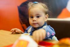 Kleines Mädchen, das Pommes-Frites im Café isst lizenzfreies stockfoto
