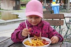 Kleines Mädchen, das Pommes-Frites isst lizenzfreie stockfotografie