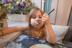 Kleines Mädchen, das Pommes-Frites mit Gabel im Restaurant isst stockbilder