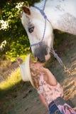 Kleines Mädchen, das Pony küßt. Lizenzfreies Stockfoto