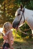 Kleines Mädchen, das Pony küßt. Stockfoto