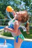 Kleines Mädchen, das am Pool wässert Stockfotos