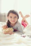 Kleines Mädchen, das Popcorn im Bett isst Lizenzfreie Stockfotos