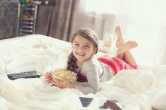 Kleines Mädchen, das Popcorn im Bett isst Stockfoto