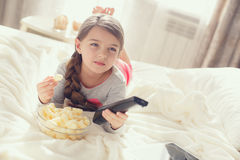 Kleines Mädchen, das Popcorn im Bett isst Lizenzfreie Stockfotografie