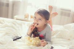 Kleines Mädchen, das Popcorn im Bett isst Stockbild
