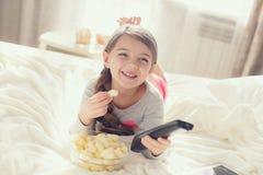 Kleines Mädchen, das Popcorn im Bett isst Lizenzfreies Stockbild