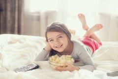Kleines Mädchen, das Popcorn im Bett isst Stockfotografie