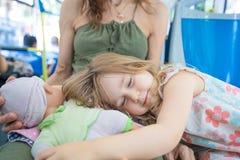 Kleines Mädchen, das Puppe auf Mutterbeinen auf dem Bus umarmend schläft Stockbilder