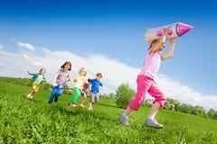 Kleines Mädchen, das Raketenkartonspielzeug und Kinderlauf hält Stockfotos