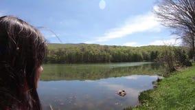 Kleines Mädchen, das am Rand von See, Ansicht des Wald-und Seepanoramas betrachtend steht stock video footage