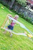 Kleines Mädchen, das riesige Seifenblase macht Stockbilder