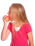 Kleines Mädchen, das roten Apfel auf Weiß isst lizenzfreies stockbild
