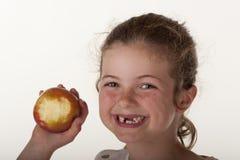 Kleines Mädchen, das roten Apfel isst Stockbild