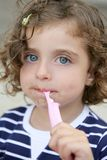 Kleines Mädchen, das süße Süßigkeit mit schmutzigem Gesicht isst Stockfotografie