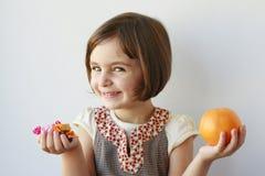 Kleines Mädchen, das Süßigkeiten oder Früchte wählt Lizenzfreie Stockbilder