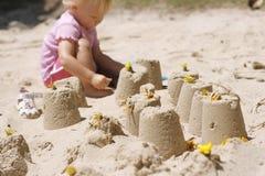 Kleines Mädchen, das Sandschlösser bildet Stockfotos