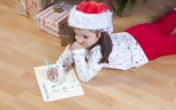 Kleines Mädchen, das Santa Letter vorbereitet stockfotos