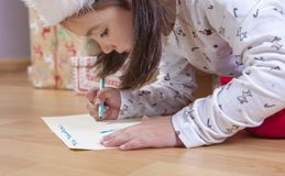 Kleines Mädchen, das Santa Letter vorbereitet stockfotografie